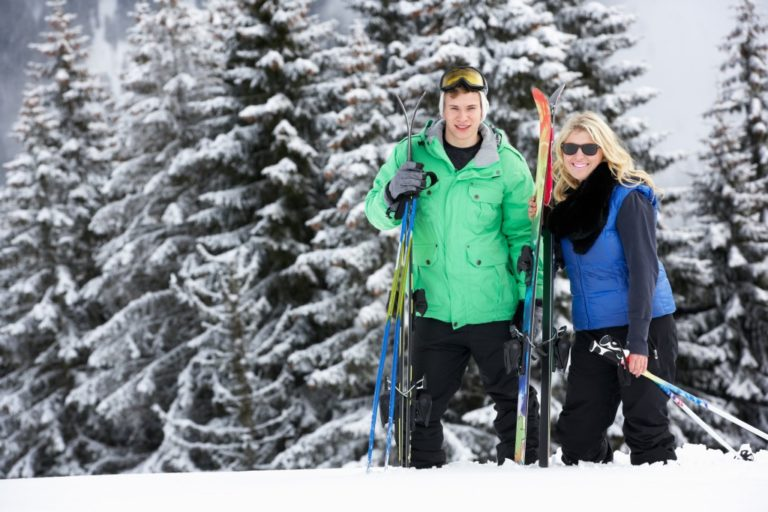 man and woman wearing layered winter clothes and holding ski poles